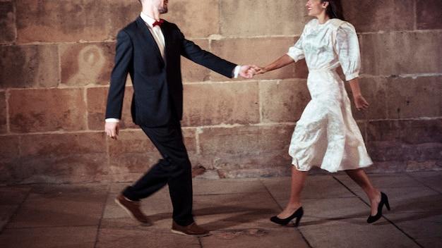 Uomo vestito che balla con la donna in strada