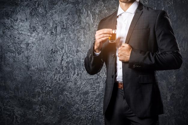Uomo vestito con un bicchiere di bevanda alcolica
