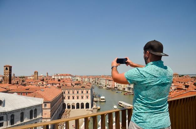 Uomo viaggio turistico in italia. equipaggi la fabbricazione della foto facendo uso del suo smartphone che sta e che guarda sulla cima del tetto. vista sul canal grande. uomo viaggio turistico in italia.