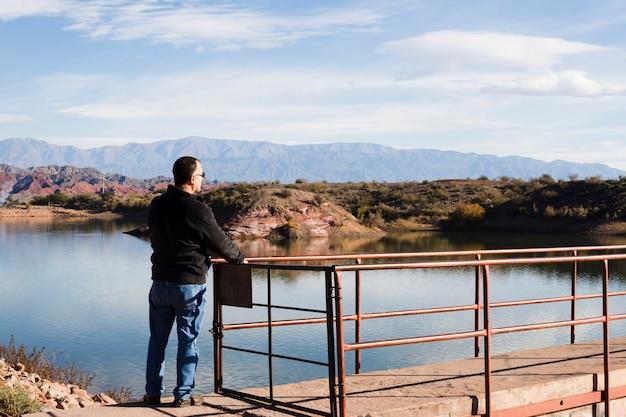 Uomo vicino al lago che gode della luce solare