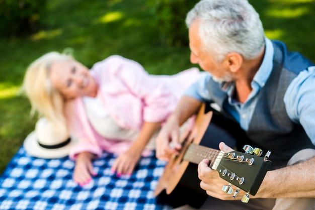 Uomo vicino di vista con la chitarra al picnic