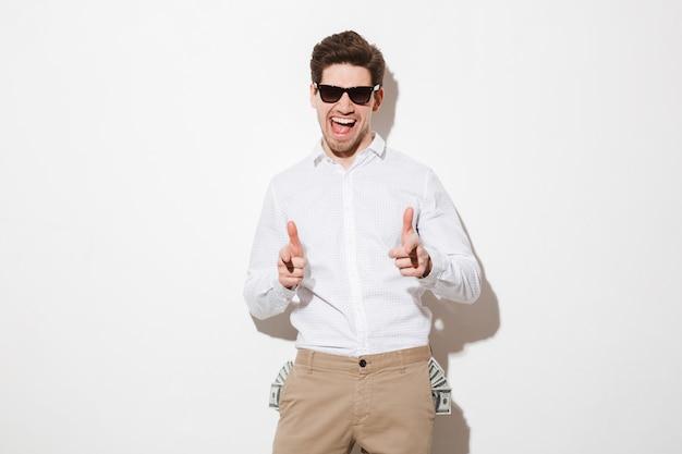 Uomo vivace in occhiali da sole neri che punta il dito indice sulla fotocamera con un sacco di soldi banconote da un dollaro sporgenti dalle tasche, isolato su uno spazio bianco con ombra