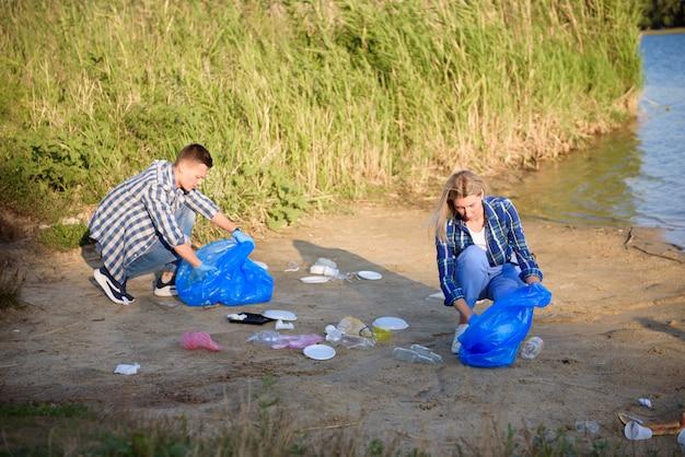 Uomo volontario che raccoglie spazzatura sulla spiaggia. concetto di ecologia.