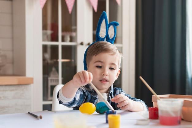Uova adorabili della pittura del ragazzino per pasqua