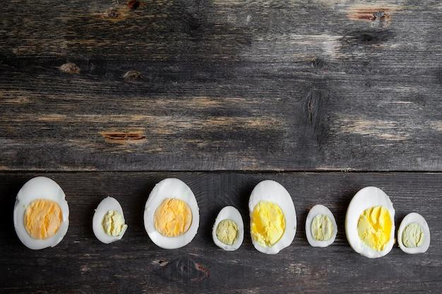 Uova affettate su vecchio fondo di legno, vista superiore.