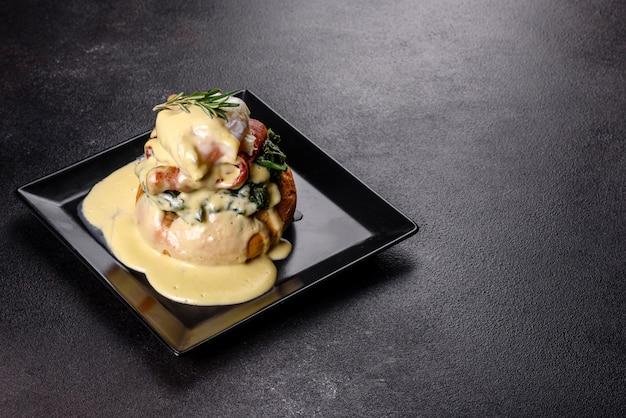 Uova alla benedict o uova alla fiorentina su una banda nera nel caffè. benedict all'uovo su muffin inglese tostato
