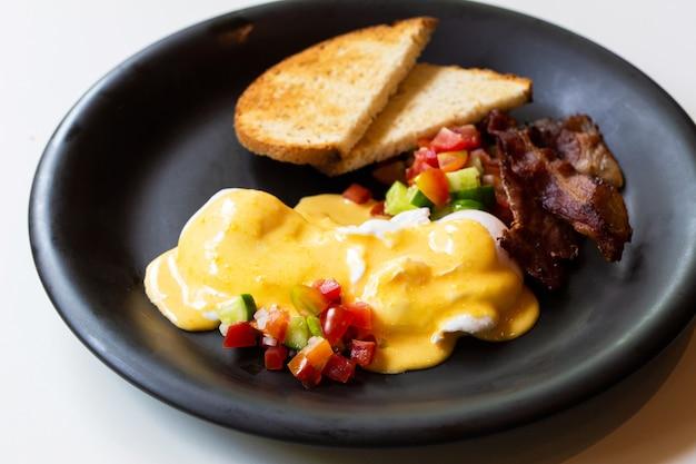 Uova alla benedict - pane, becon e pomodoro, uova in camicia e deliziosa salsa burrosa olandese