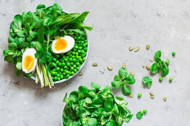 Uova alla coque con lattuga, aglio orsino, piselli e prezzemolo. diventa vegano