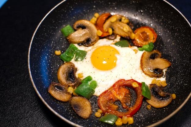 Uova appena fritte con verdure in padella