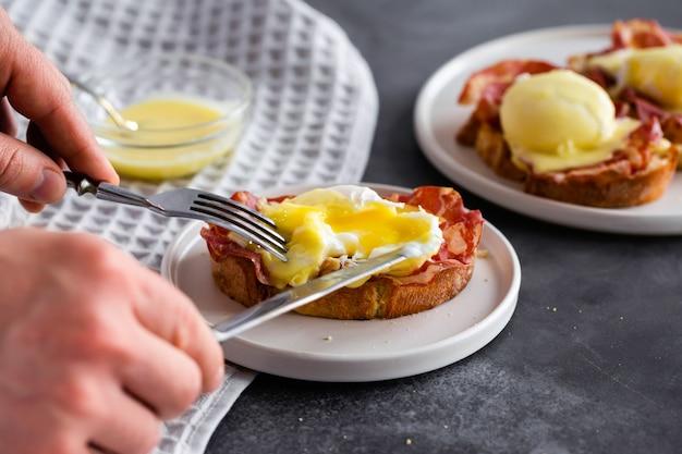 Uova benedict: pane tostato inglese, prosciutto crudo, uova in camicia con salsa olandese e limone su grigio