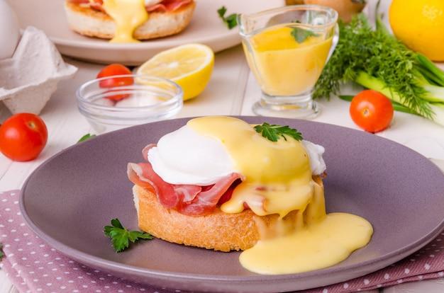 Uova benedict sulla tavola di legno bianca