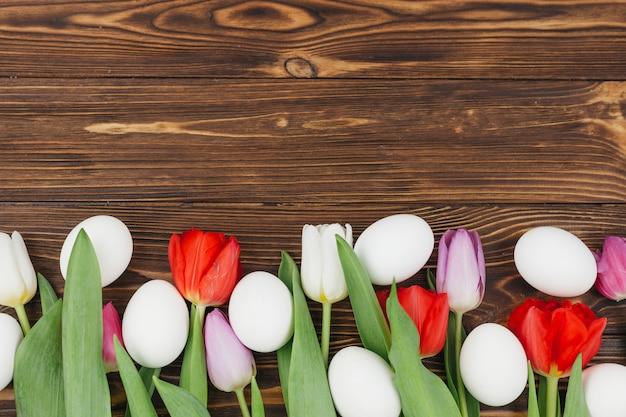 Uova bianche con tulipani sul tavolo