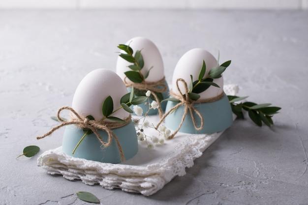 Uova bianche del pollo con la decorazione di pasqua su un tovagliolo bianco. tendenza arredamento casa