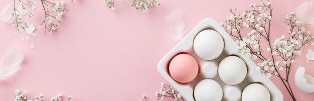 Uova bianche in supporto e fiori ceramici bianchi sulla tavola rosa