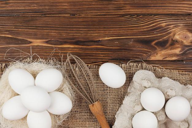 Uova bianche nel nido e nel rack con la frusta sul tavolo