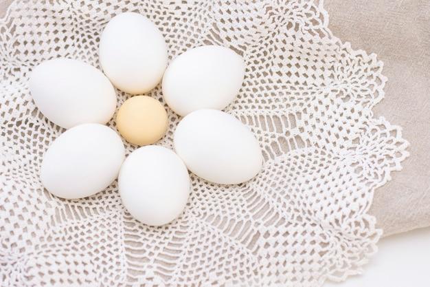Uova bianche organiche di nutrizione sana di freschezza del pollo su una borsa marrone e un bello tovagliolo tricottato bianco sotto forma di un fiore.