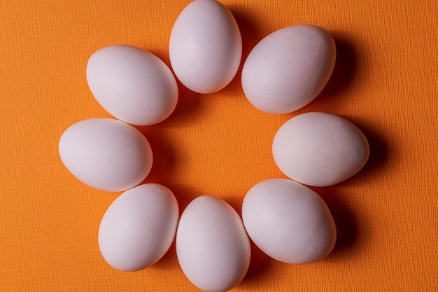 Uova bianche organiche in un crudo su backgound pastello arancio.