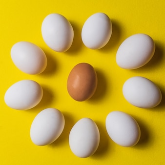 Uova bianche organiche in un crudo su backgound pastello giallo.