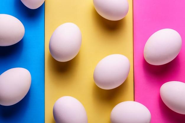 Uova bianche organiche in un crudo su backgound pastello.