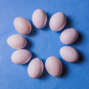 Uova bianche organiche su backgound pastello.