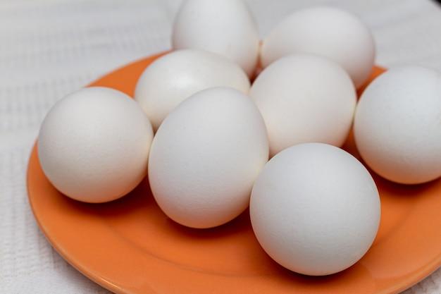 Uova bianche sulla fine arancio del piatto su