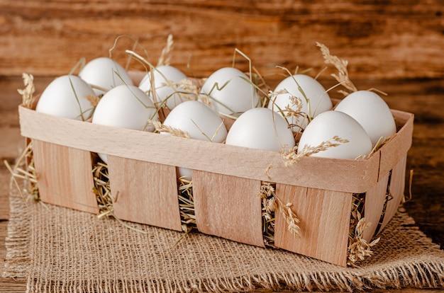 Uova biologiche fresche in contenitore su uno spazio di legno. copia spazio