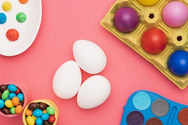 Uova colorate distese e strumenti da colorare