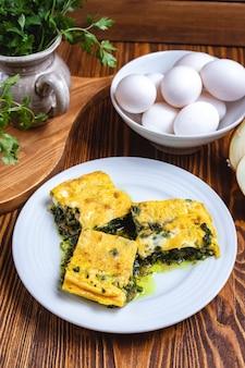 Uova con la vista laterale delle spezie di verdure di spinaci