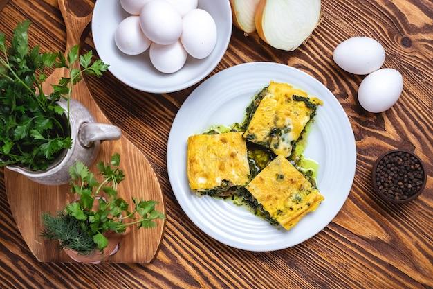 Uova con la vista superiore delle spezie di verdure della cipolla degli spinaci