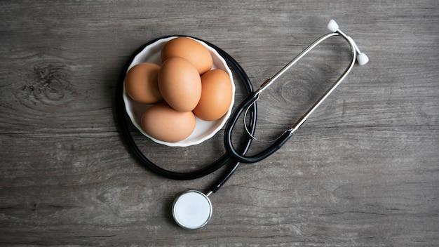 Uova con lo stetoscopio sulla tavola di legno nel concetto sano dell'alimento.