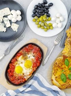 Uova con pomodori, formaggio, olive e pane