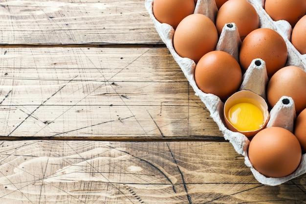 Uova crude marroni in confezione di fabbrica su legno rustico