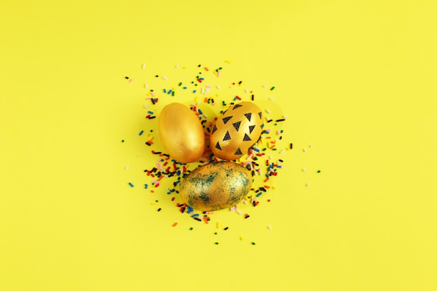 Uova d'oro con caramelle colorate spruzza