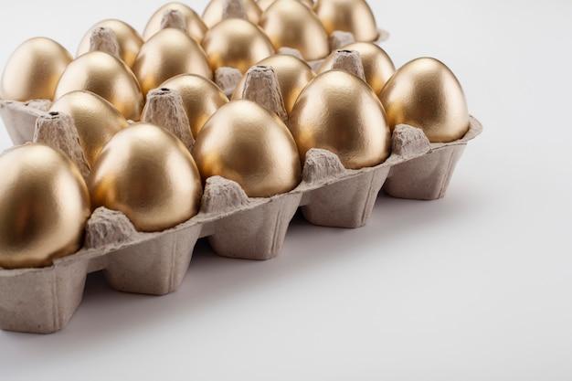 Uova d'oro in una cassetta, su sfondo bianco. il concetto di pasqua.