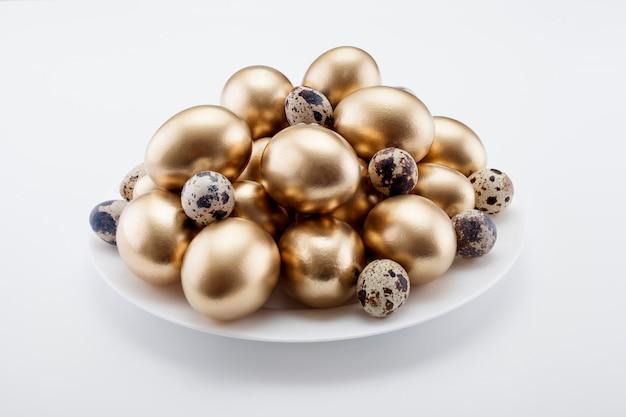 Uova d'oro mescolate con quaglie in un piatto. il concetto di pasqua.