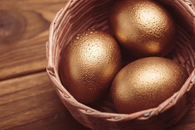 Uova d'oro sul tavolo di legno