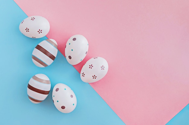 Uova decorate con strisce e fiori su sfondo rosa e blu, concetto di pasqua.