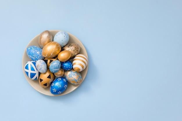 Uova decorate dorate alla moda di pasqua sul piatto grigio isolato sulla superficie del blu. alla moda piatto giaceva pasqua.