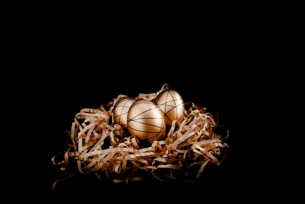 Uova decorate dorate di pasqua in nido. buona pasqua