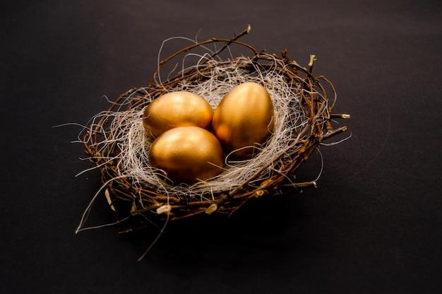 Uova decorate dorate di pasqua su sfondo scuro.