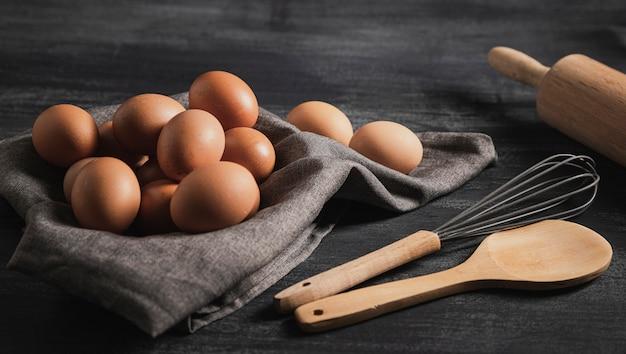 Uova del primo piano sul panno e sugli strumenti della cucina