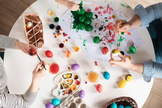 Uova della pittura della famiglia di vista superiore per pasqua