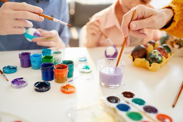 Uova della pittura della famiglia per la fine di pasqua in su