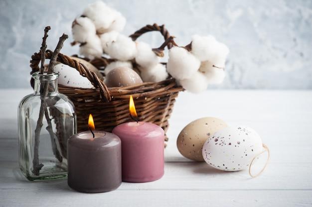 Uova di brown, canestro di vimini nella composizione rustica di pasqua con le candele accese sulla tavola di legno bianca.