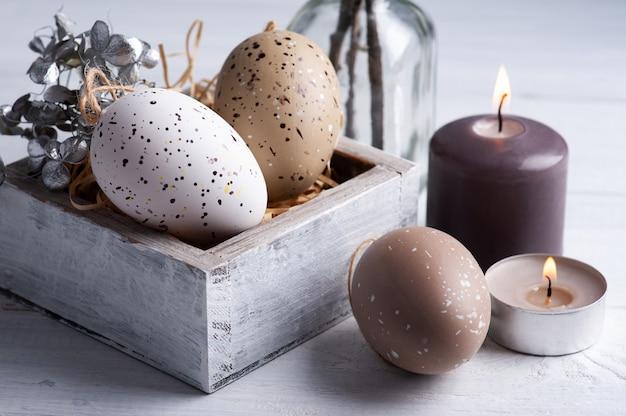 Uova di brown e candele accese nella composizione rustica di pasqua sulla tavola di legno bianca. decorazione in stile scandinavo per biglietto di auguri