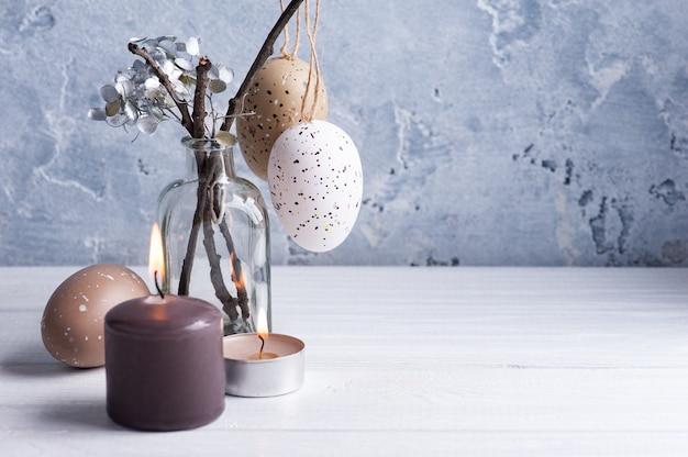 Uova di brown e candele accese nella composizione rustica di pasqua sulla tavola di legno bianca.