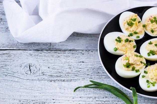Uova di casa ripiene di formaggio e granchio condite con cipolle verdi