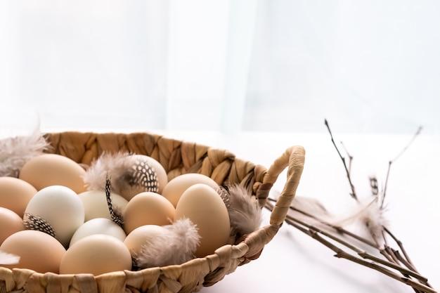 Uova di chiken organiche dell'azienda agricola cruda fresca in un canestro su bianco