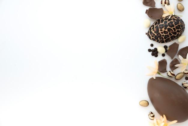 Uova di cioccolato di pasqua con i fiori sul tavolo