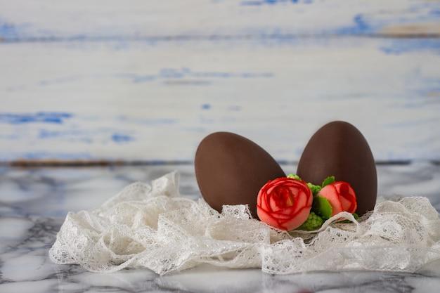 Uova di cioccolato, nastro di pizzo bianco, rose decorative artificiali sulla superficie di legno bianca. concetto di pasqua